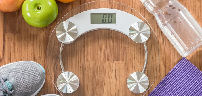 Weighing scale with fruits, grey shoes and bottled water