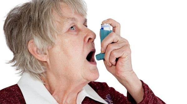 Senior woman spraying anti asthma on her mouth