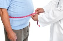 Doctor measuring mans stomach fats