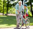 Happy grandfather teaching his grandson to bike