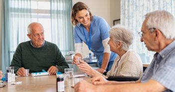 Nurse giving medicine to group of seniors